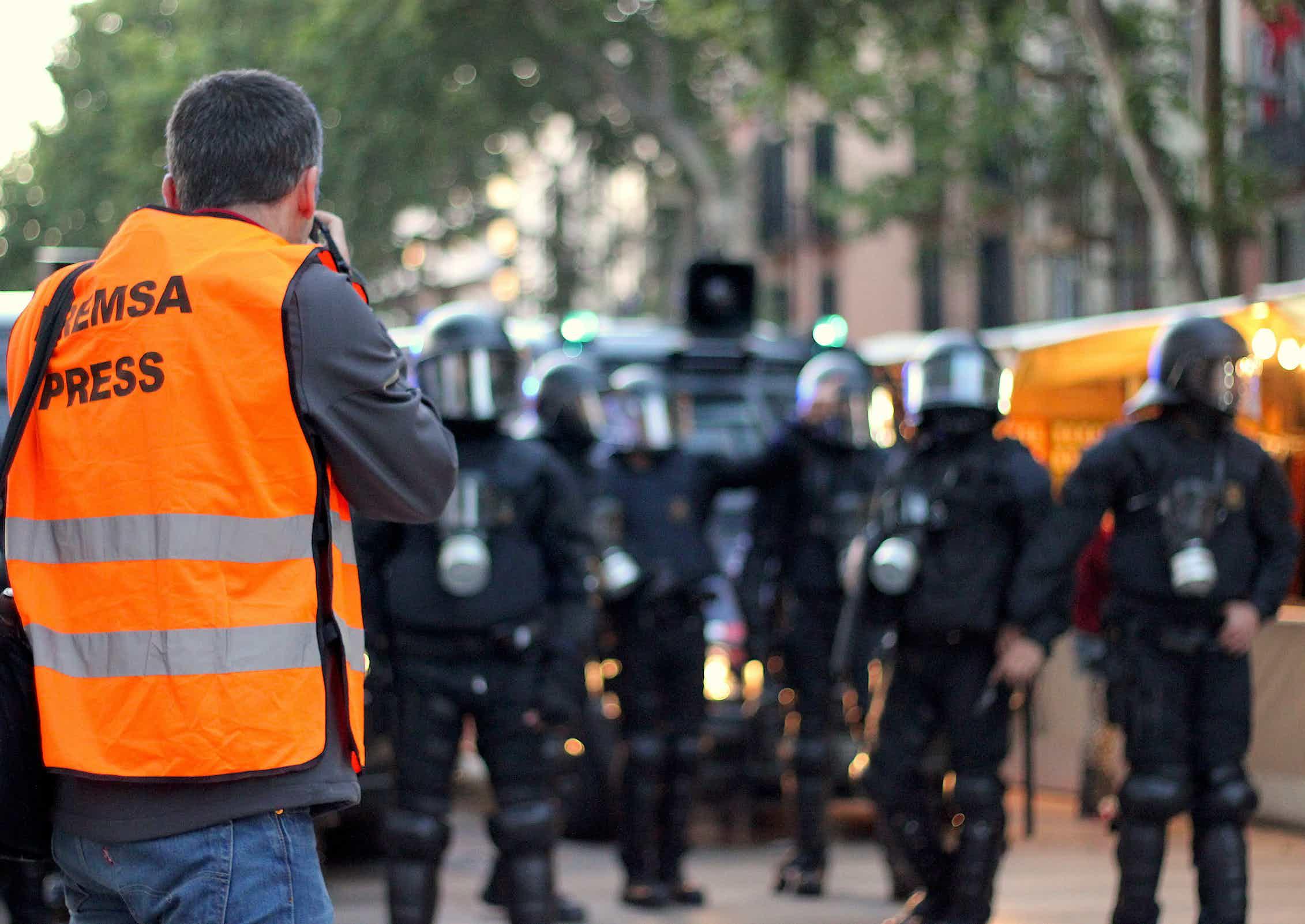 Fotoperiodista trabaja ante varios policías durante un desalojo en Barcelona en 2014.Shutterstock / VCalvo - Control