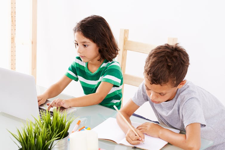 Two children working on homework at table