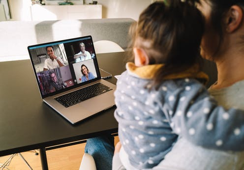 Woman holding baby in video conference on laptop with four people