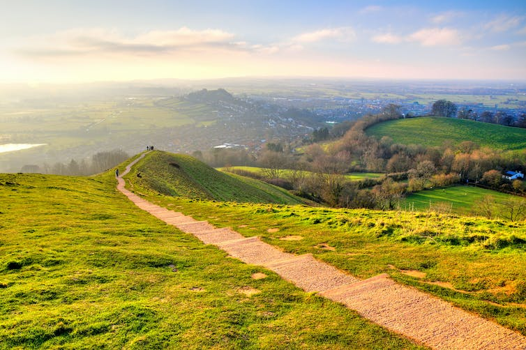 Large green field with path running through it in Glastonbury, UK