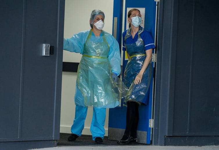 Two hospital staff wearing PPE.
