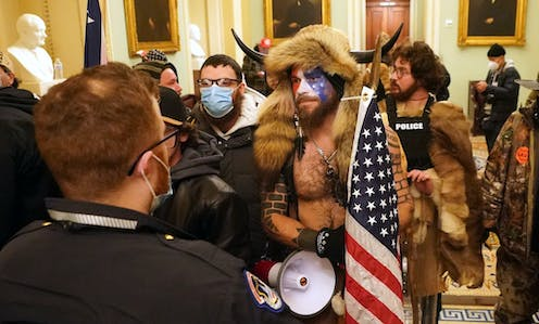 Man wearing fur hat with horns, carrying US flag, surrounded by rioters in the US Capitol Building, January 6 2021.