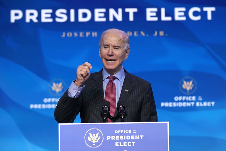 Joe Biden giving a speech under a sign that says 'President Elect.'
