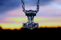Pendant representing Thor's hammer, against the background of a colourful sunset.