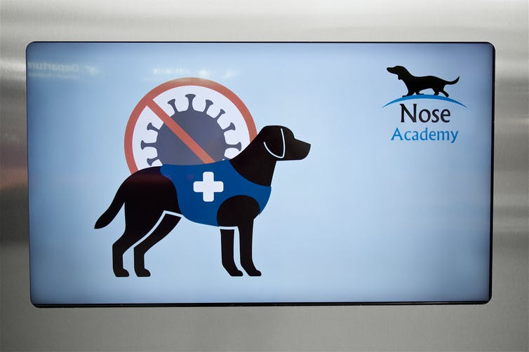 Sign showing images of a dog and the SARS-CoV-2 virus.