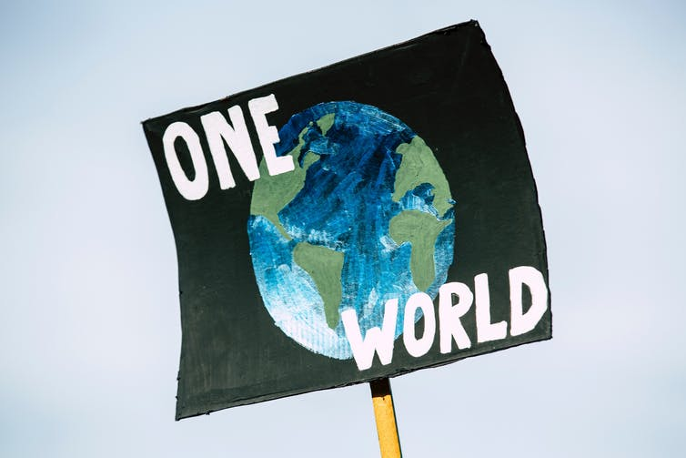 Black placard with 'one world' written on it.