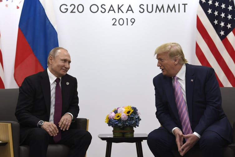 Trump chats with Putin with U.S. and Russian flags behind them.