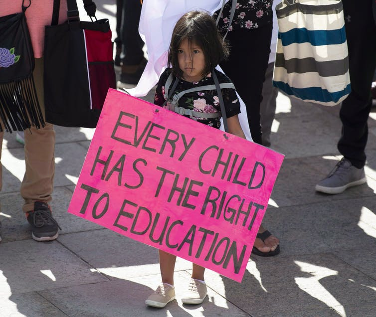 A young girl holds a sign during a protest. The sign reads: every child has the right to education.