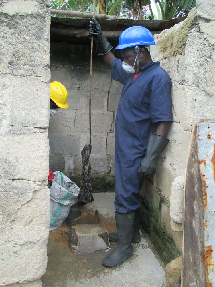 A man emptying a pit latrine in urban Tanzania
