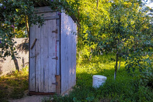 An wooden outhouse with a bucket beside it