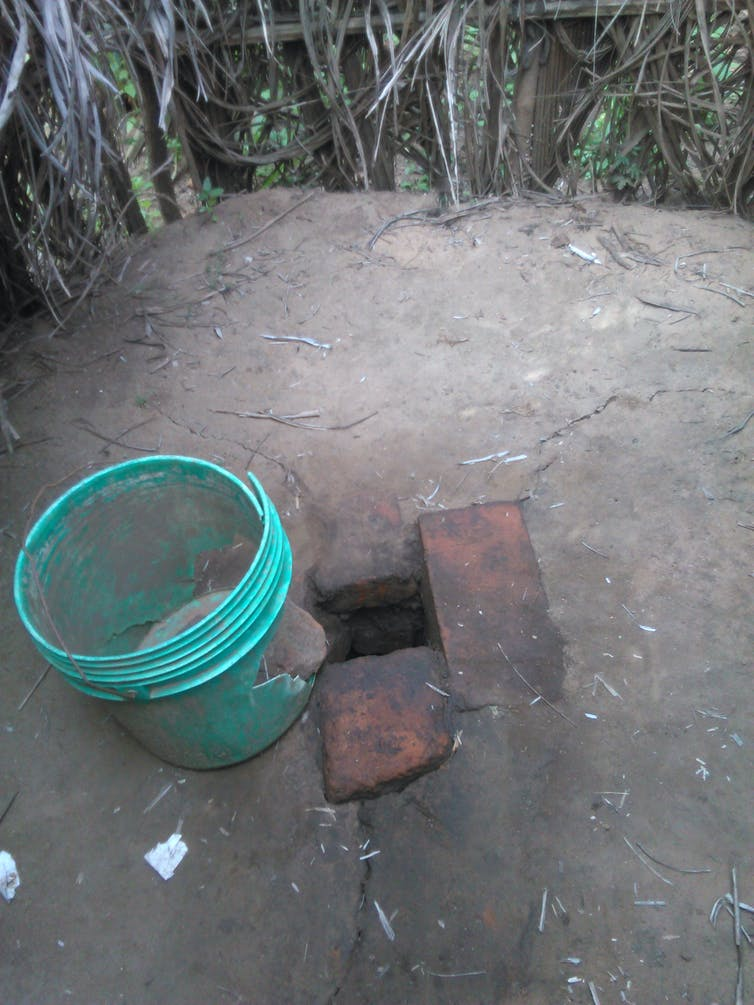 A hole in the ground, lined with two bricks, and a blue bucket beside it