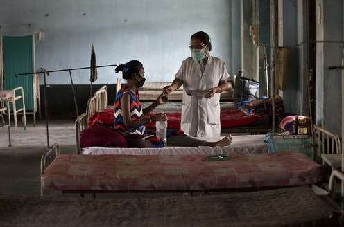 A woman receives TB medication in a clinic.