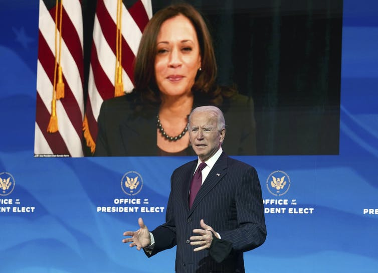 Joe Biden speaks from a stage with Kamala Harris on video screen behind him.