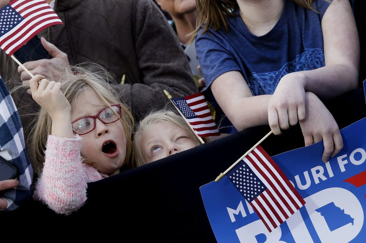 Children, one wearing red eyeglasses, wave U.S. flags.