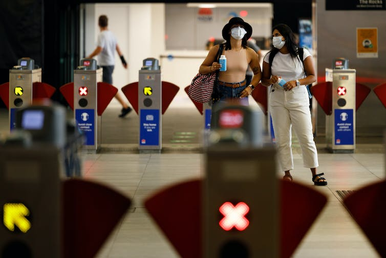 People wearing facemasks at a train station in Sydney