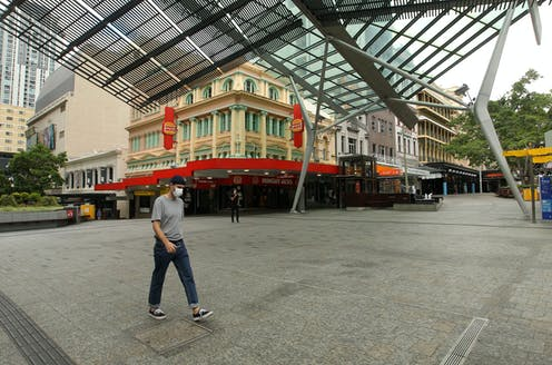 Person wearing a mask walking through deserted Brisbane streets