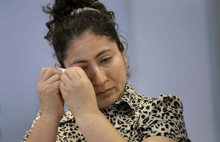 A Guatemalan mother cries at a news conference.