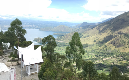 Aerial view of Urat village, with mountains in the backdrop and 2 indigenous houses painted white.