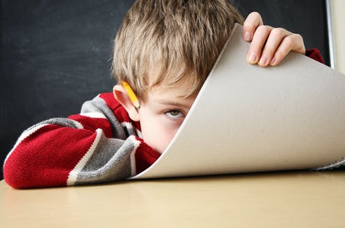 Un niño con cara aburrida, un lapicero sobre la oreja mira a cámara mientras se tapa media cara con un folio.