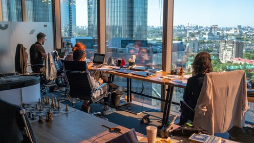 Office workers sit at desks gazing out of window.