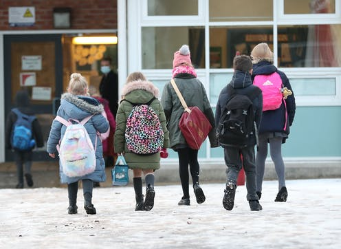 Five children wearing backpacks enter a school.