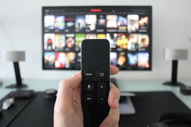 Hand in focus holding remote with a blurred TV in the background
