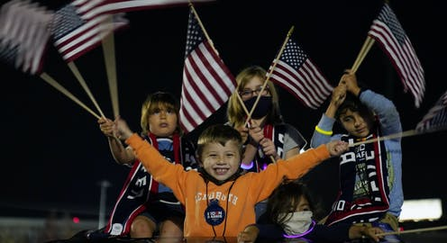 Children wave American flags at a night-time event.