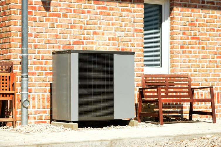 Air heat pump for heating and hot water in front of an apartment building.