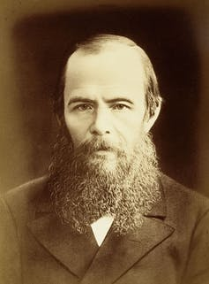 Sporting a beard, Dostoyevsky stares solemnly into the camera.