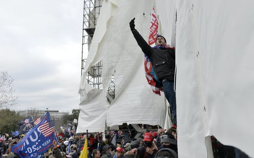 A man hanging from scaffolding raises his middle finger.