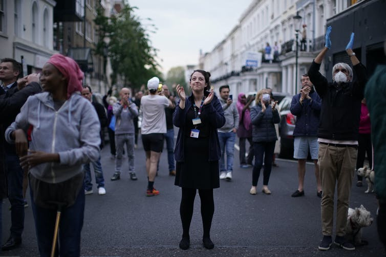 People stand in a London street and applaud.