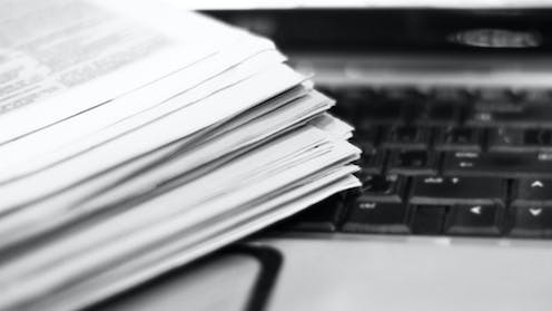 A close-up of a stack of papers and a keyboard