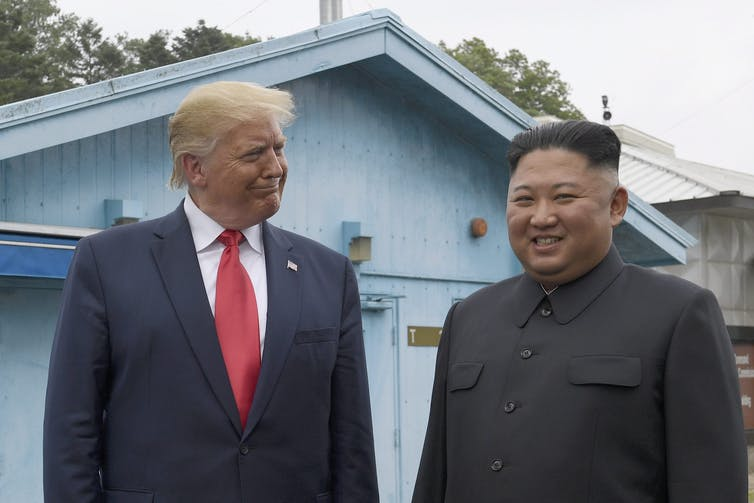 Trump smiles at North Korean leader Kim Jong Un.