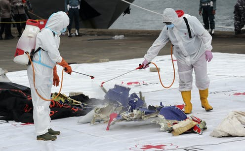 Workers disinfect parts of Sriwijaya Air Flight 182 recovered from the waters off Jakarta, Indonesia, January 10 2021.