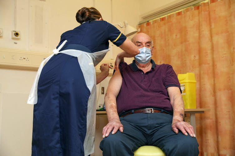 Person receiving the Oxford-AstraZeneca COVID vaccine in England.