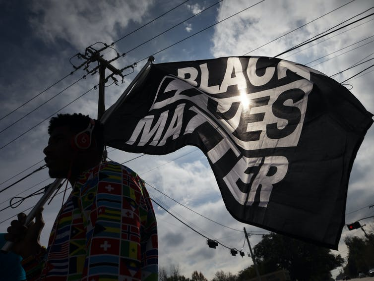 Protester carrying a 'Black Lives Matter' flag