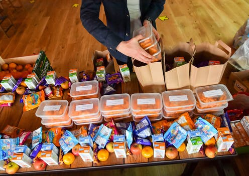 A man packs brown bags of food for families in need.