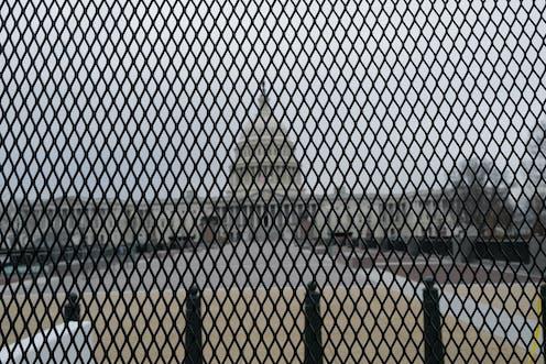 El edificio del Capitolio de los Estados Unidos se adivina tras una reja tupida.