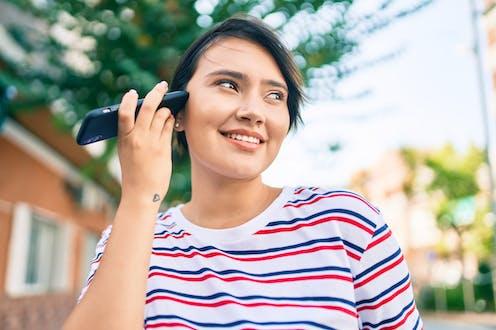 Una mujer joven escucha un mensaje de voz acercando a su oído  su teléfono móvil.