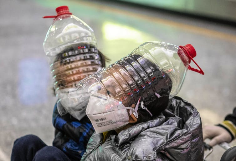 Boys wearing protection masks, gloves and modified water bottles over heads.