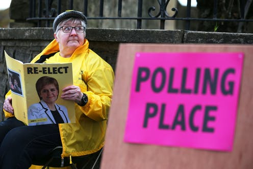 A womam reading SNP election literature