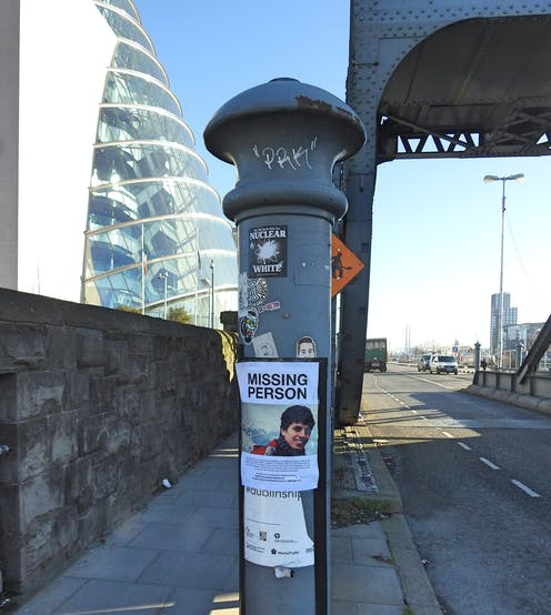 Poster of a missing person on a metal pillar in the middle of a street with a glass building and a metal bridge in the background