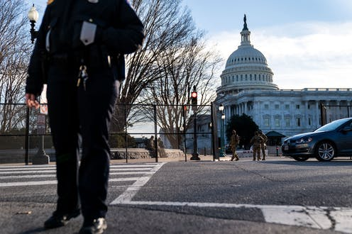 A U.S. Capitol Police Officer stands at a street corner near the U.S. Capitol as heightened security measures are put in place around the U.S. Capitol Building a day after a pro-Trump mob broke into the nations capitol while Congress voted to certify the 2020 Election Results.