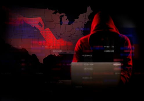 Hooded man on laptop codes in front of map of USA