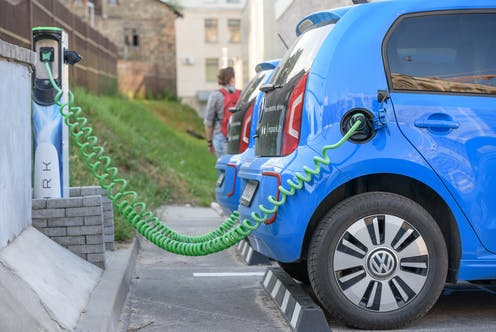 Electric car Volkswagen e-Up charging its batteries on a parking. Spark car sharing service in Lithuania.