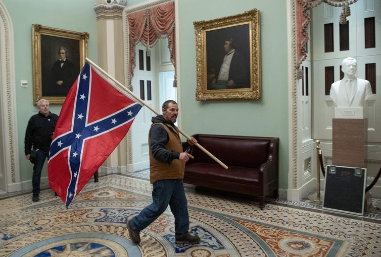 A man carries the Confederate battle flag in the U.S. Capitol.