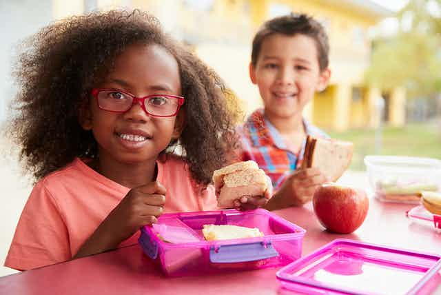Two children eating packed lunches