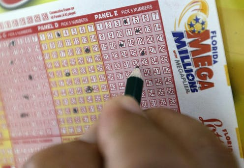 A hand filling out a Mega Millions lotto card.