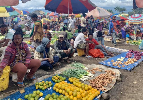 A women is sitting next to several men at a market where they are selling a wide range of produce.