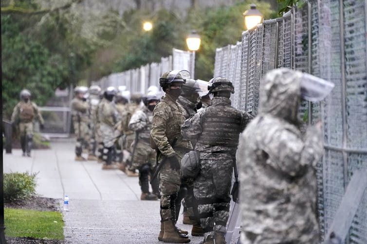 National Guard troops stand along a chain link fence.
